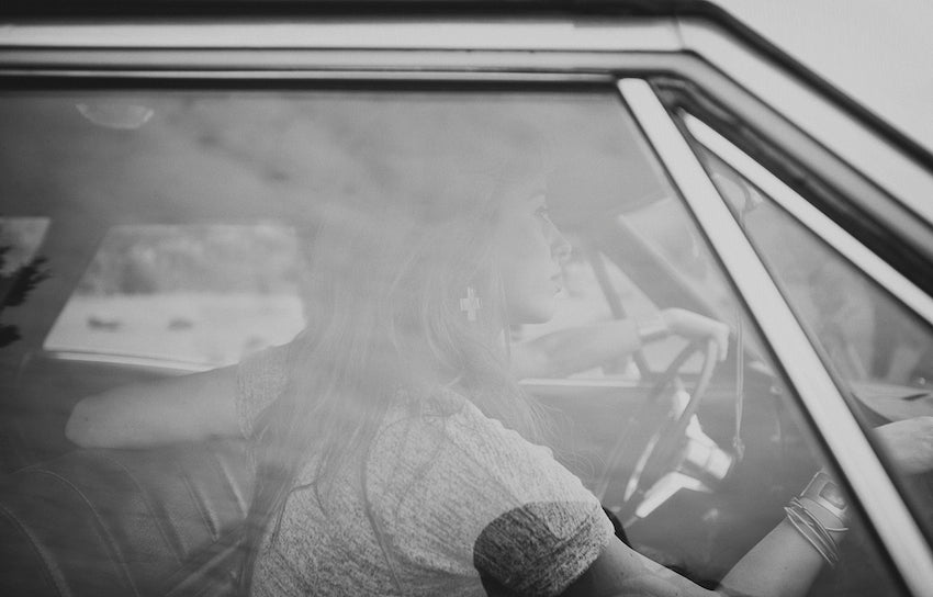 Black and white photograph of models in the car, old timey looking.
