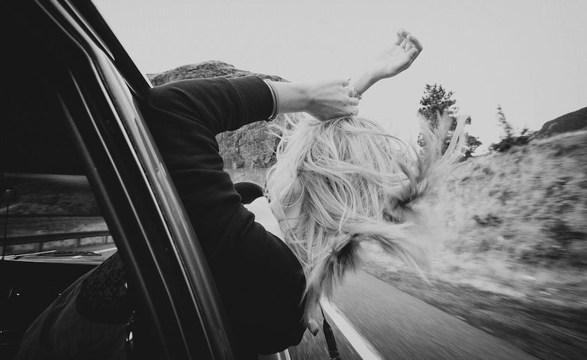 Model's hair blowing in the wind as she sticks her head out of a moving car.