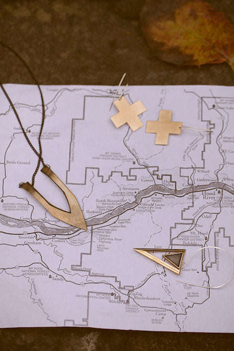 Geometric jewelry pointing to specific places on a map.