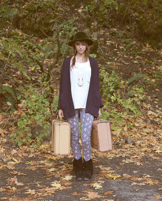 A model wearing hip clothing with two suitcases in her hands, ready for an adventure.