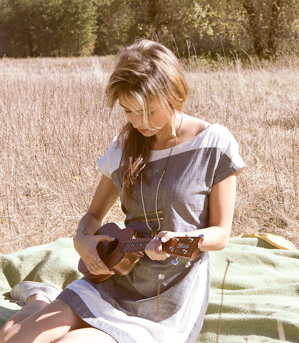 A betsy and iya model playing ukelele in the sun.