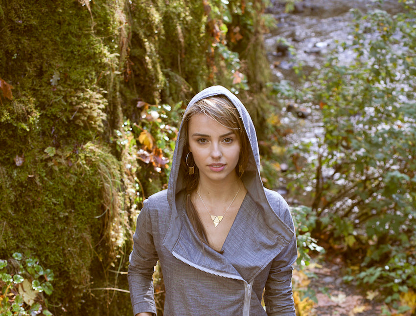 Model wearing betsy & iya jewelry in the woods.