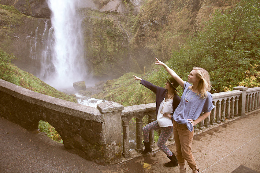 Two models doing a Lewis and Clark pose at Multnomah Falls.