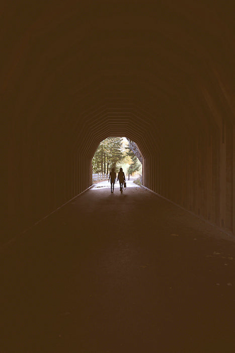 Mysterious photo of two models on the other side of a tunnel with the light behind them.