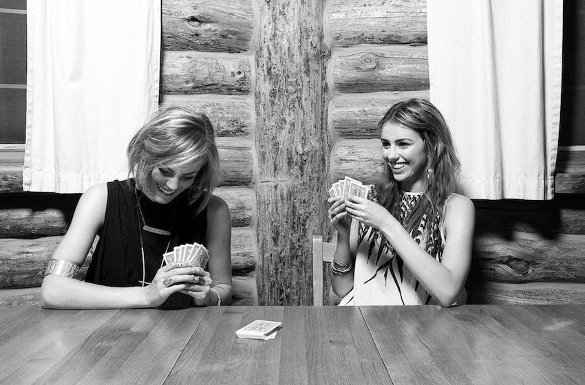 Models giggling while playing cards in a cabin.