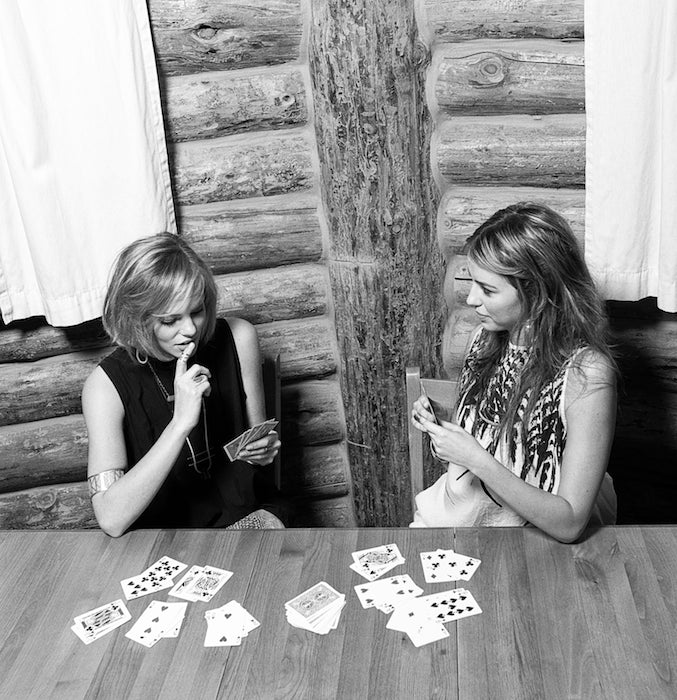 Two models playing cars in a cabin wearing lots of betsy & iya jewelry.