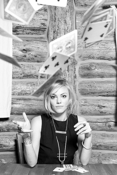 Model throws her playing cards at the camera.