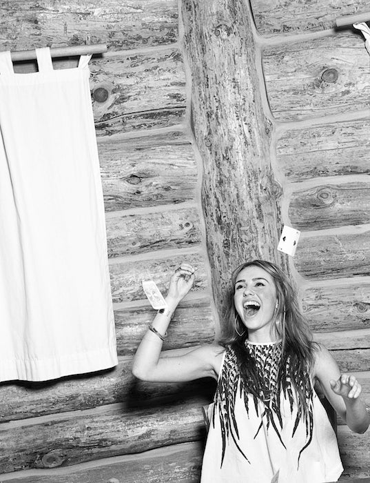 Model throws her playing cards up in the air and laughs.