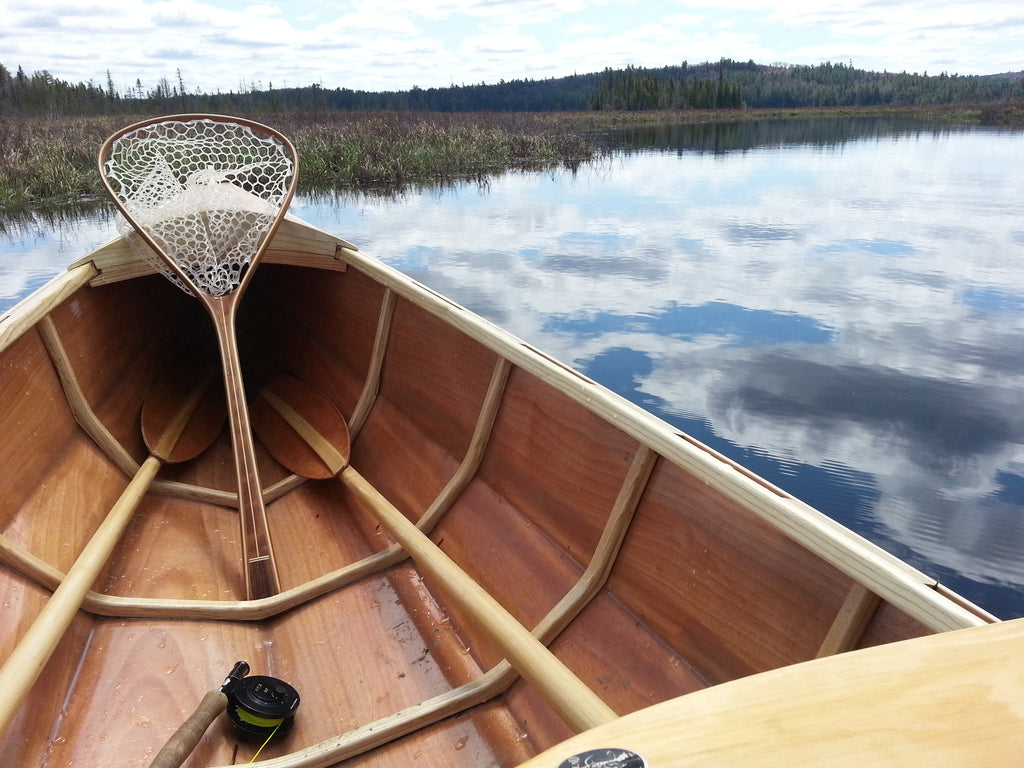 Tailwater Outdoors premium quality classic style fishing nets, handmade from high quality woods. Ideal for all fishing and outdoor enthusiasts. Shot of net in a canoe on the water