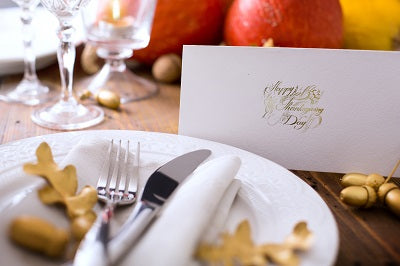 Formal white printed table place cards for holiday guests written in gold ink