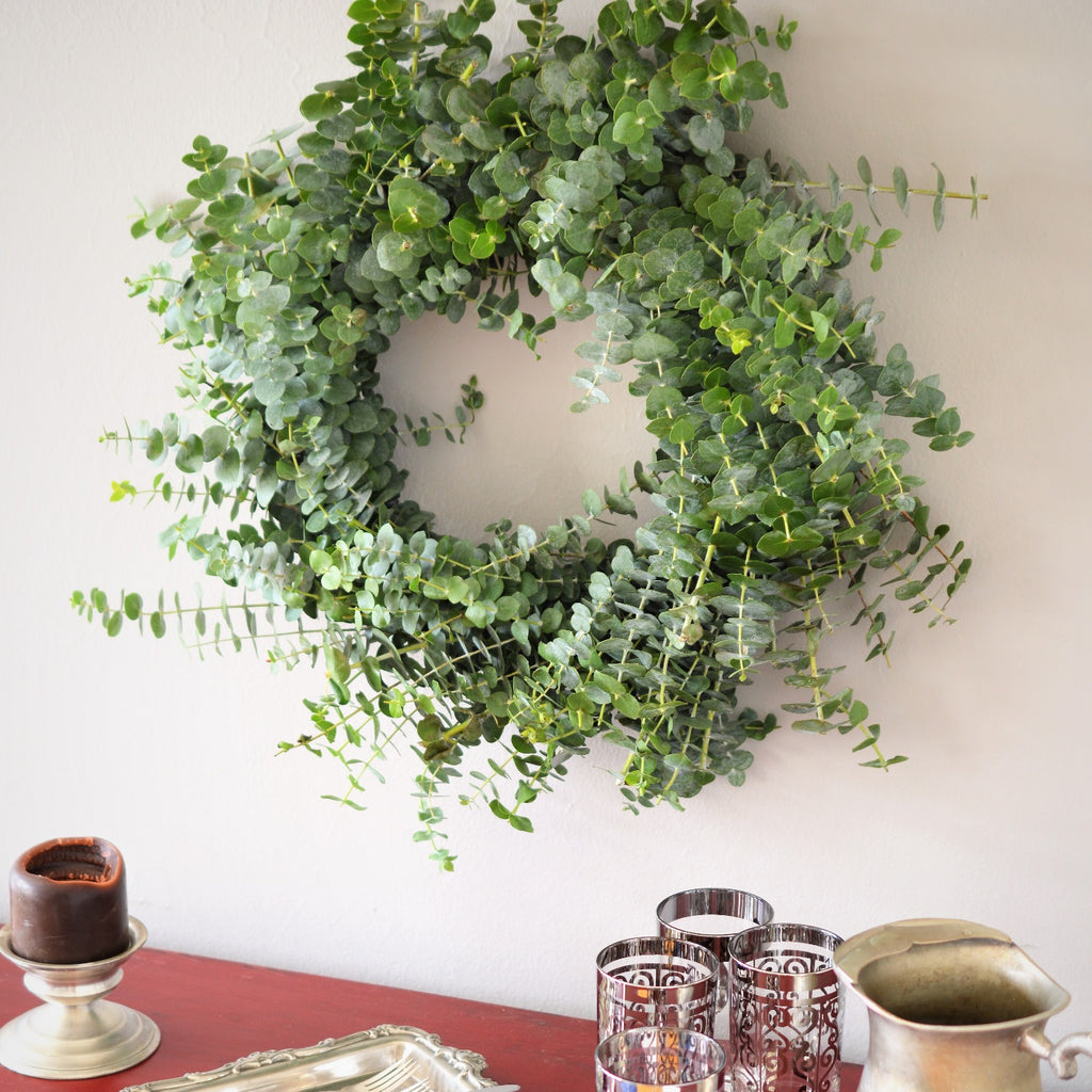 Baby Eucalyptus Wreath | Club Botanic | Indoor Baby Eucalyptus Wreath hanging on white wall above red buffet | Fresh Eucalyptus Wreath for Wedding