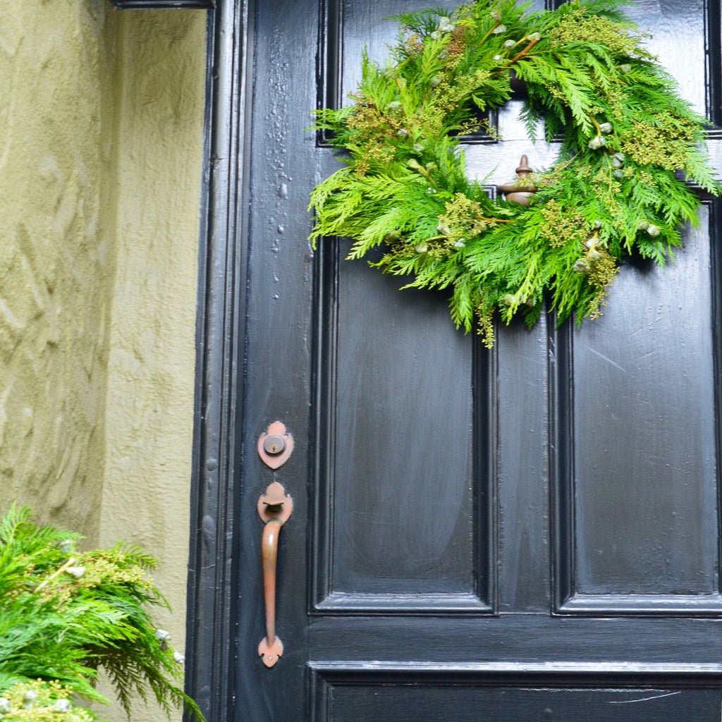 Mendocino Holiday Cedar Wreath | Club Botanic | Traditional Black Wooden Door with Fresh Green Cedar Wreath for Christmas | Eucalyptus Pod Wreath | Naked Eucalyptus Wreath Outside
