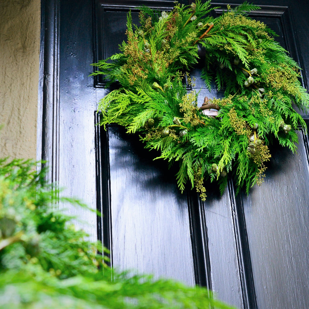 Mendocino Holiday Cedar Wreath | Club Botanic | Fresh Green Holiday Wreath | Fresh Green Wreath for the holidays | Cedar and Stripped Eucalyptus Wreath hanging on black wooden door | Outdoor Holiday Wreath Fresh Green Cedar | Funeral Wreath