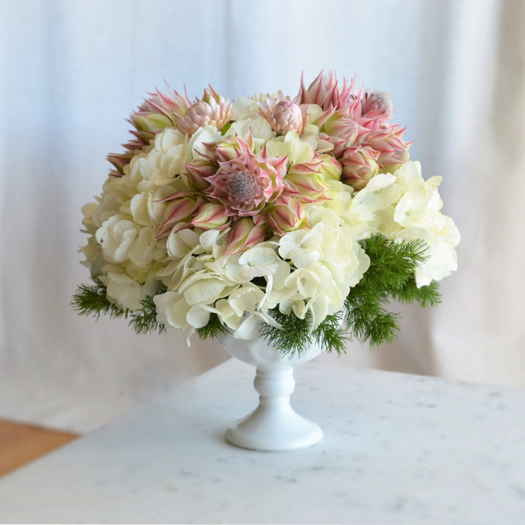 Flower arrangement with white hydrangeas and pink blushing bride protea