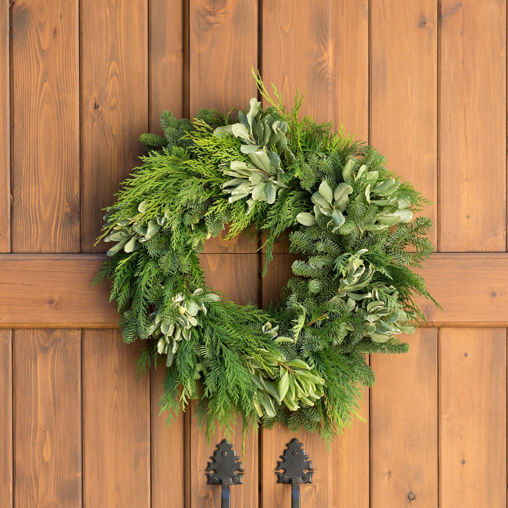 California Greens Holiday Wreath | Club Botanic | Fresh Green Cedar Wreath for Christmas | Fresh Green Cedar Wreath for the Holidays | Cedar and Pine Wreath for Christmas | Cedar and Pine Wreath for the Holidays | Outdoor Cedar Wreath on Wood Garage Door