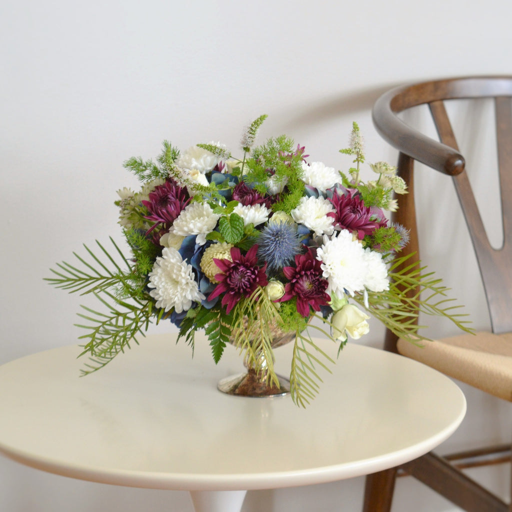 White and Purple Mums with Thistle and Spray Roses in a Golden Urn.