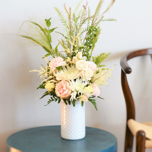 Linear flower arrangement in a tall white vase with pink garden roses, white spider mums and green foliage