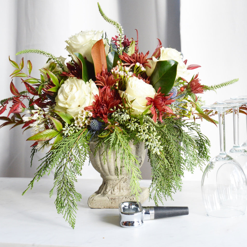 Ellen holiday blooms with white garden roses, seeded eucalyptus, cedar and veronica in a concrete urn.