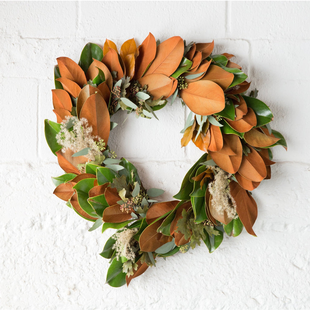 Magnolia and Eucalyptus Wreath | Club Botanic | Seeded Eucalyptus Wreath with Magnolia Leaf and Dried Green Oak Leaves | Dried Oak Leaf Wreath with Magnolia and Seeded Eucalyptus hanging on brick wall painted white |