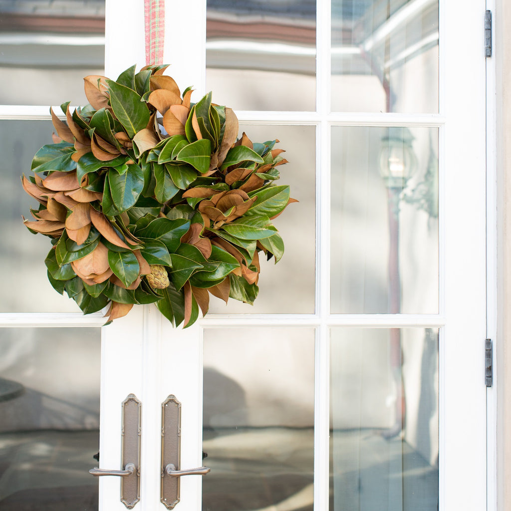 Golden Magnolia Wreath | Club Botanic | Verdant Green Magnolia Wreath hung outside | Outdoor Magnolia Wreath | Seasonal Fresh Magnolia Wreath | Magnolia Leaf Wreath | Funeral Wreath