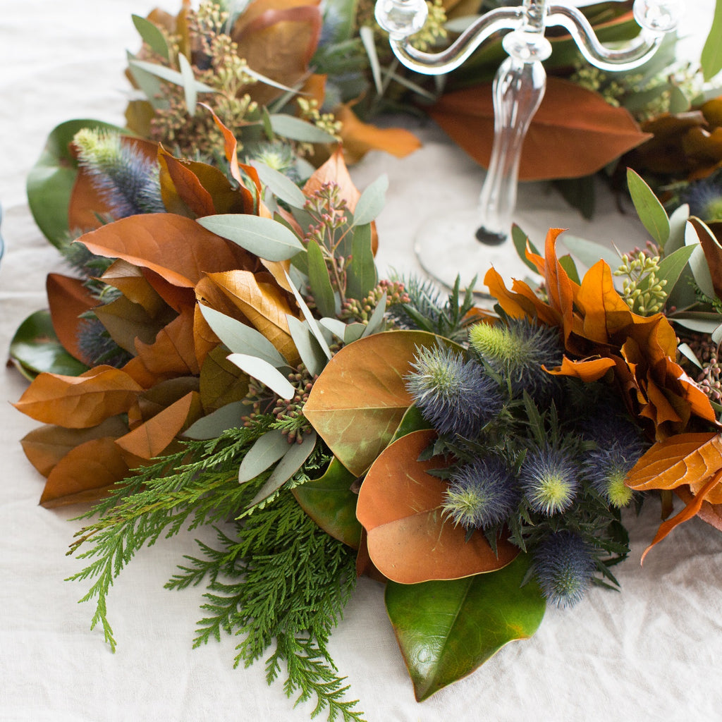 Hillsborough Estate Fresh Wreath | Club Botanic | Blue Thistle Wreath with Seeded Eucalyptus setting on table with white tablecloth