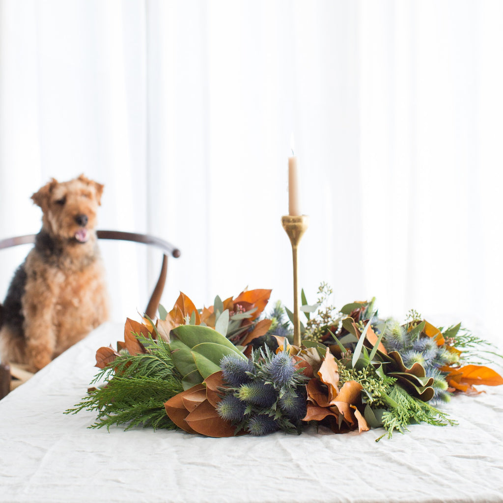 Hillsborough Estate Fresh Wreath | Club Botanic | Fresh wreath as tablescape | Fresh wreath setting on white table with Welsh Terrier | Magnolia and Cedar Wreath as table centerpiece with candle in the middle