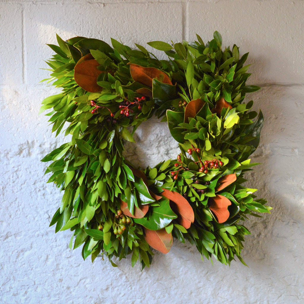 Square Laurel and Magnolia Wreath | Club Botanic | Square Fresh Wreath Bay Leaves | Bay Leaf Wreath Square | Magnolia Wreath Square | Square Magnolia Leaf Wreath | Square Bay Leaf Wreath | Eucalyptus Pod Wreath Square with Magnolia and Bay on white brick wall
