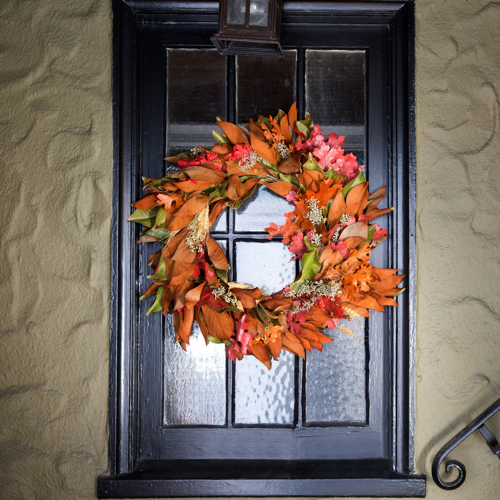 Magnolia and Red Oak Wreath | Club Botanic | Copper Oak Leaves and Red Oak Leaves combined with Magnolia Leaves in an outdoor wreath hung over a window with black wood mullions | Outdoor Fall Wreath Magnolia Leaf and Red Oak | Holiday Wreath for windows with Magnolia and oak