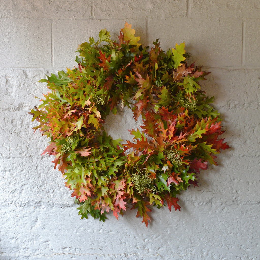 Oak and Seeded Eucalyptus Wreath | Club Botanic | Fall Leaf Wreath | Autumn Leaves and Eucalyptus Wreath | Fall Colored Leaves and Eucalyptus Pods in fresh wreath on brick wall painted white.