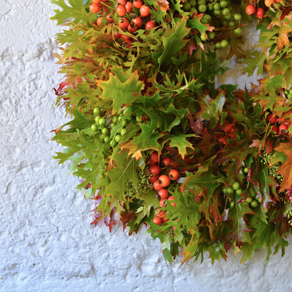 Pepperberry and Rosehip Wreath | Club Botanic | Autumn Wreath with fresh oak leaves | fall wreath with fresh colored oak leaves | Oak leaf wreath for fall | Autumn colored wreath with red and yellow oak leaves, pepperberries, rosehips and chinaberries
