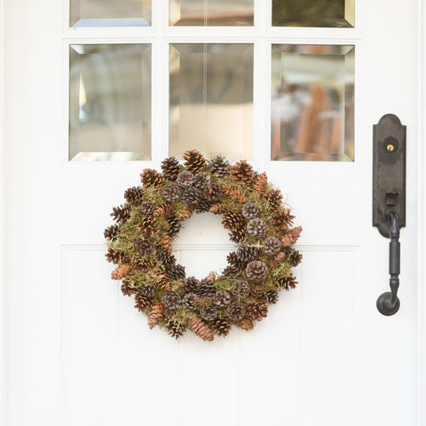 Pinecone Wreath with pine cones situated among moss and walnuts, hung on white door for the holidays