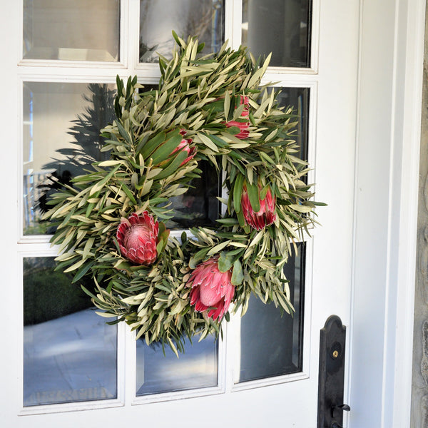 Queen Protea and Olive Wreath | Club Botanic | Protea Wreath | Wreath Protea | Fresh Wreath Olive | Queen Protea Fresh Wreath | Red and Green Wreath | Pink Wreath | Wreath with Pink | Wreath with Red | Olive and Protea Wreath hanging arm of a chair in mansion foyer