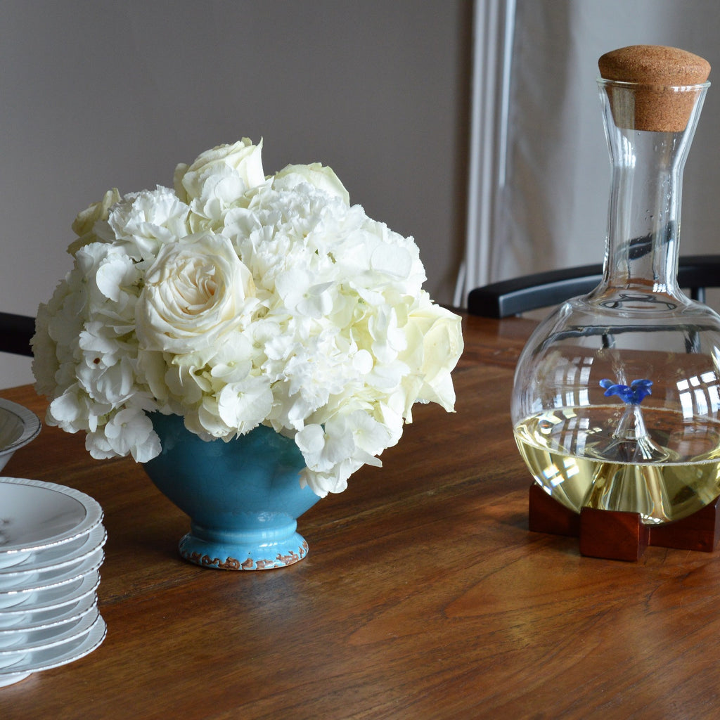 Retta Winter White Floral Arrangement, displayed on a set table with wine, it's made of solid white flowers including white garden roses, white hydrangeas and white spray roses in a french blue container