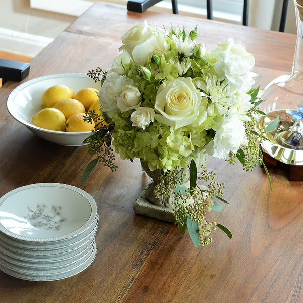 Ruth Garden Arrangement with green hydrangeas, white roses and seeded eucalyptus setting on dinner table