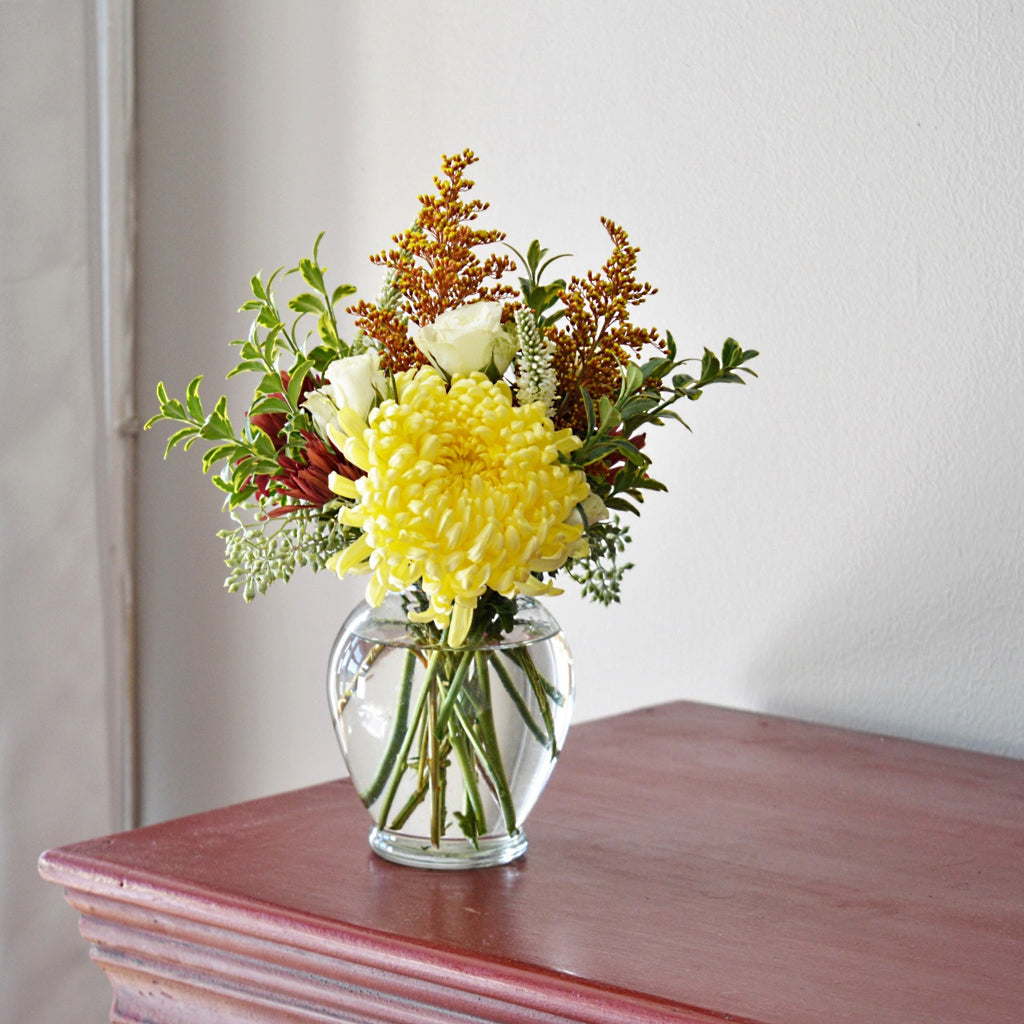 Small bouquet with yellow spider mums, white spray rose, solidago, and boxwood setting on a red console