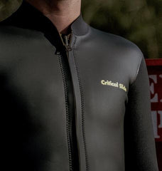 Mans chest in a black Critial Slide Society Wetsuit Jacket with zipper up the front