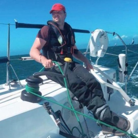 Oscar Mead, founder of TeamO Marine, sailing whilst wearing one of his own TeamO Offshore lifejackets on a sunny day in the English Channel