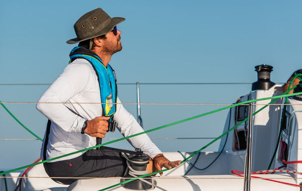 A sailor wearing a TeamO lifejacket, looking at the sails of the yacht whilst trimming the jib sail using a Harken winch