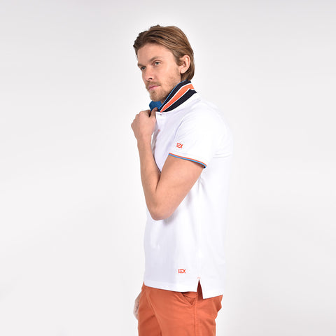 White polo with embroidered orange EX logo on left sleeve and bottom hem; reversible navy collar; and striped, ribbed armbands.