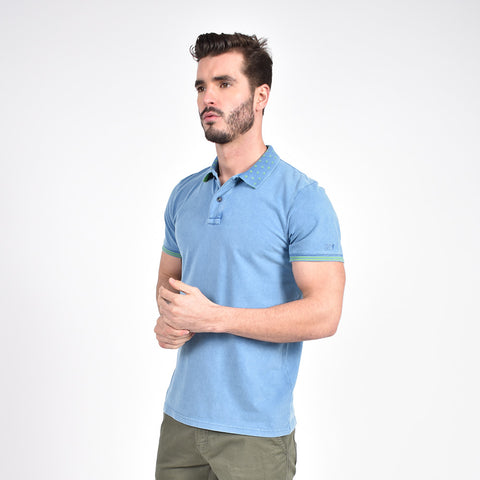 Model in powder-blue polo with striped, ribbed armbands and jacquard, diamond grid collar.