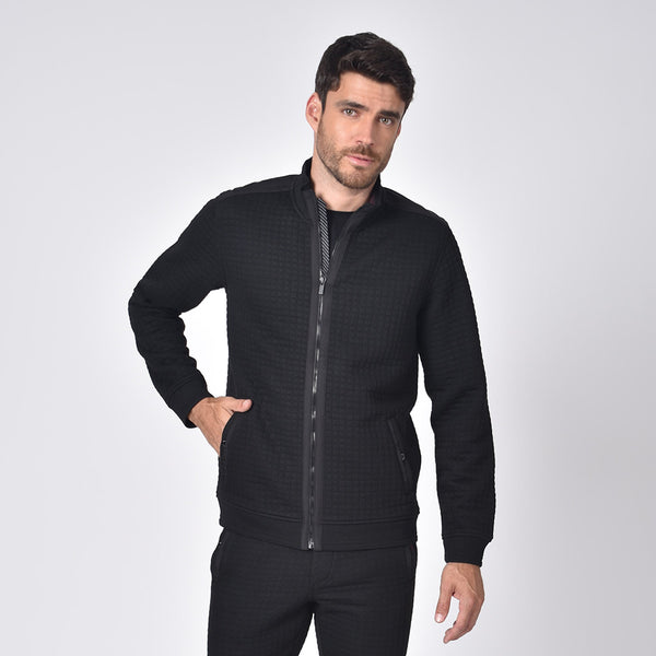 Model in black, quilted track jacket with full front-zipper and front snap-button pockets.