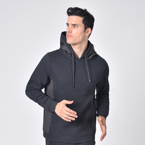 Model in grey, quilted hoodie with side zip-pockets and a drawstring hood.