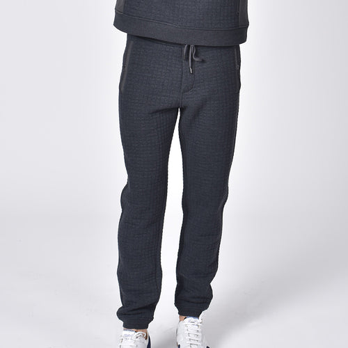 Grey, quilted cotton joggers with tapered fit, snap-button pockets, and drawstring waist.