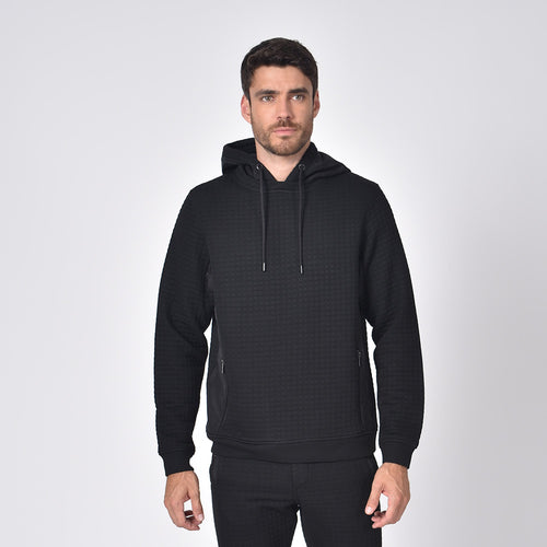 Model in black, quilted hoodie with side zip-pockets and a drawstring hood.