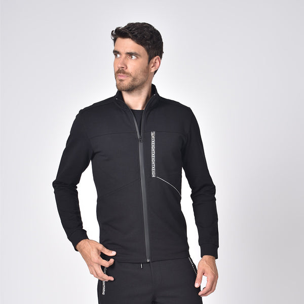 Model in black, cotton track jacket with hidden, full front-zipper; grey piping detail; and logo-lined chest zip-pocket.