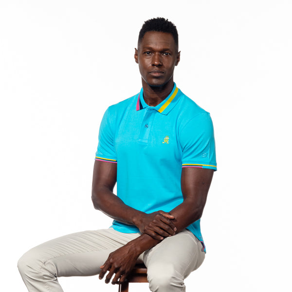 Seated model wearing bright blue polo with block-striped collar.