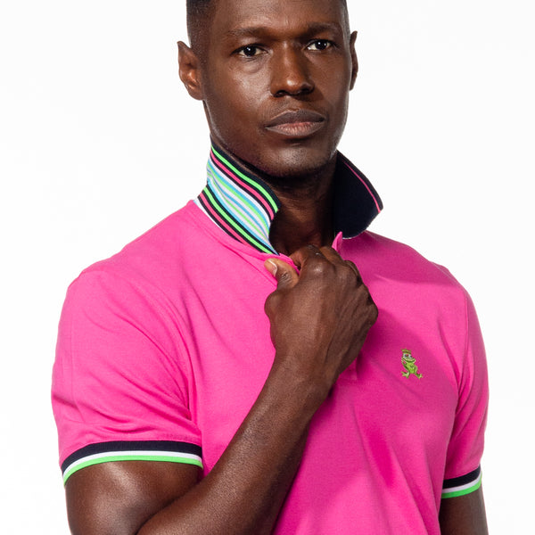 Model wearing fuchsia polo with flipped, striped collar.