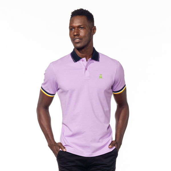 Model posing in lilac polo with navy collar, striped armbands, and embroidered green frog mascot.