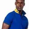 Model in royal-blue polo with reversible paisley-print collar in yellow.