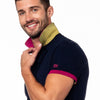 Model in navy polo with fuchsia ribbed armband; embroidered fuchsia EX logo; and reversible collar with yellow grid pattern.